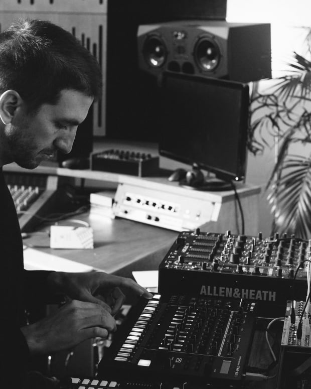 A photo of Alex Banks in his Brighton studio making leftfield bass music, and playing on a drum machine.