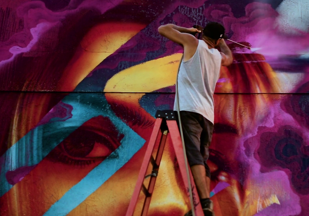 In a groundbreaking process, graffiti artist Fluke uses a high-pressure sprayer to remove paint, exposing new layers of mural beneath.
