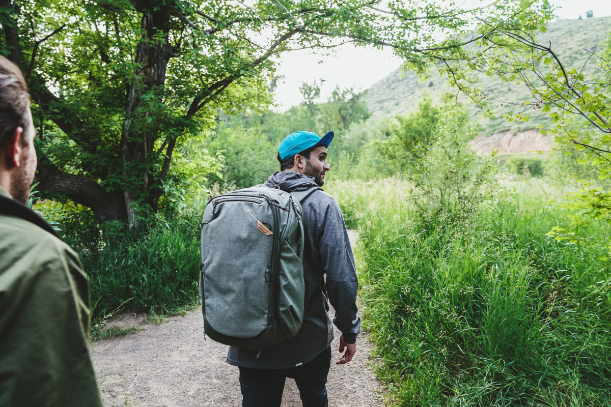 Cam wears 45L Travel Bag by Peak Design, Merino Hoodie by Chrome, Hat by Ciele and Regular Stretch Chino Trousers  by Goldwin