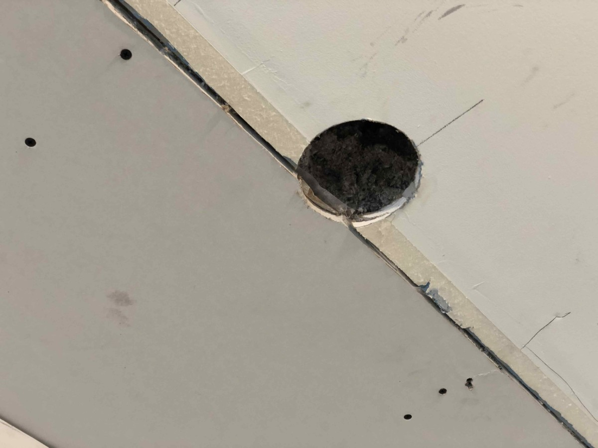 The hole in the ceiling where the cellulose insulation was sprayed.