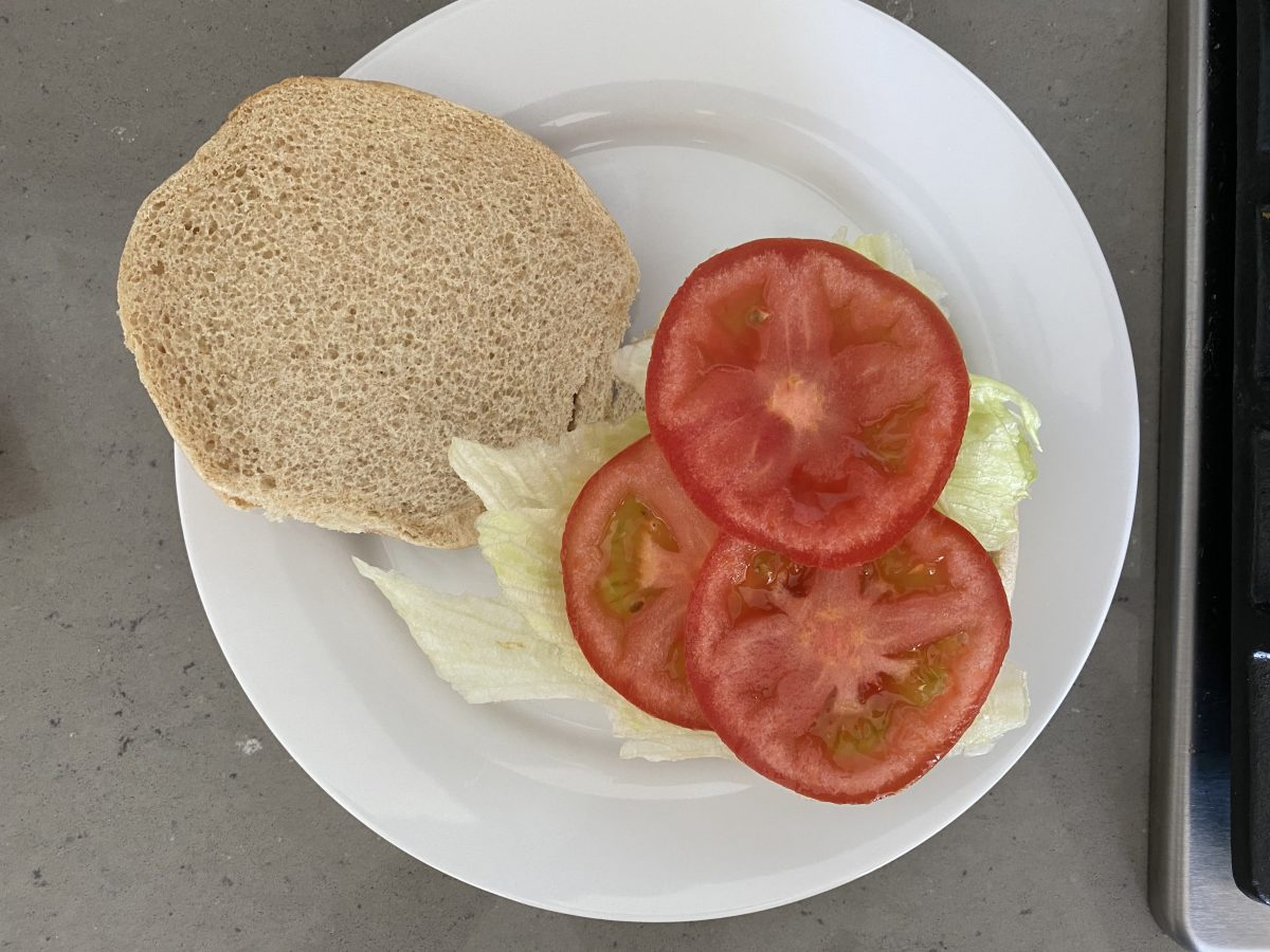 Keep the tomatoes on the top to stabilize your creation, put vegan dressing on top bun.